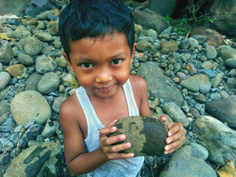 People and Nature.Asian kid holding stone in the river side stock photos