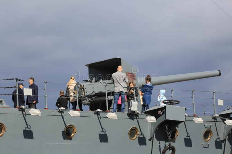 People near a ship`s gun on a cloudy sky background royalty free stock photo