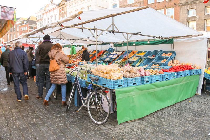 People near vegetable stalls on the market square. Den Bosch, Netherlands - January 17, 2015: People near vegetable stalls on the market square in Dutch town Den royalty free stock photography