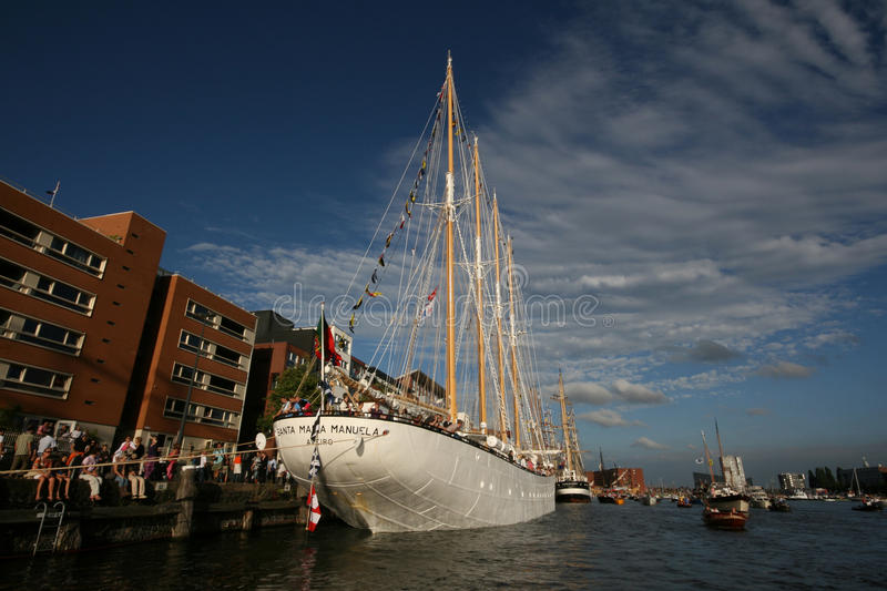 People next to a huge four-master ship moored on the canal. Crowd next to a huge four-master ship moored on the canal in front of buildings during Sail Amsterdam royalty free stock image