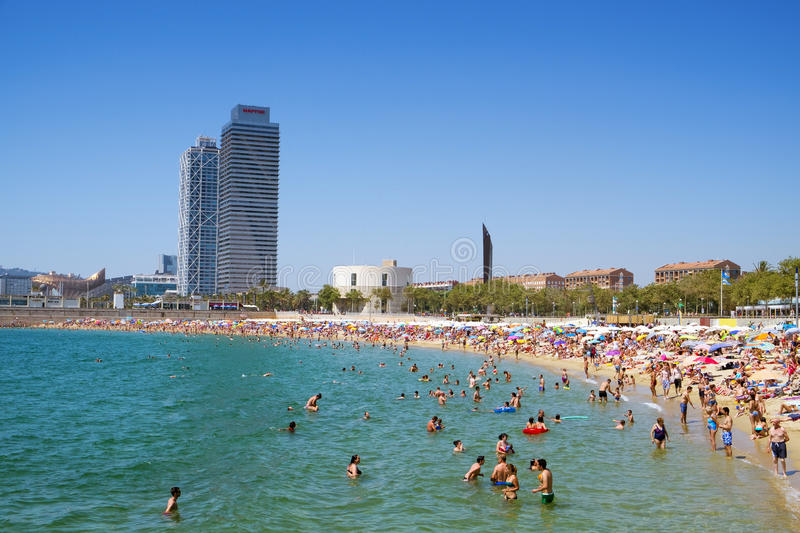 People at Nova Icaria Beach, in Barcelona, Spain. BARCELONA, SPAIN - JULY 10: People at Nova Icaria Beach on July 10, 2016 in Barcelona, Spain, and Hotel Arts royalty free stock photography
