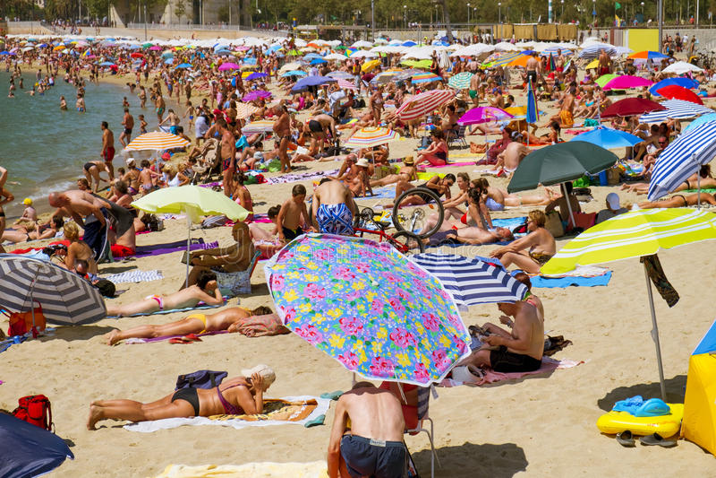 People at Nova Icaria Beach, in Barcelona, Spain. BARCELONA, SPAIN - JULY 10: People sunbathing at Nova Icaria Beach on July 10, 2016 in Barcelona, Spain. This royalty free stock photo