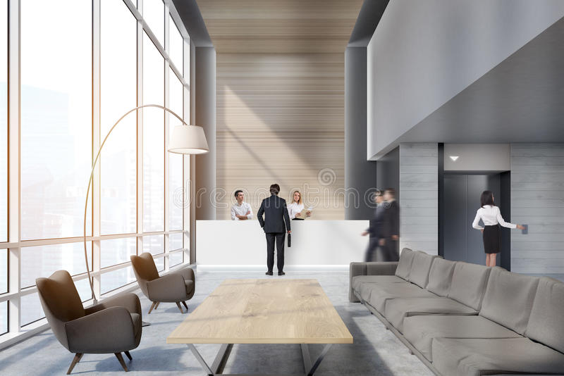 People in an office waiting area. People in the office waiting area with sofas, armchairs, large wooden table and a reception counter. An elevator is seen in the royalty free stock photos