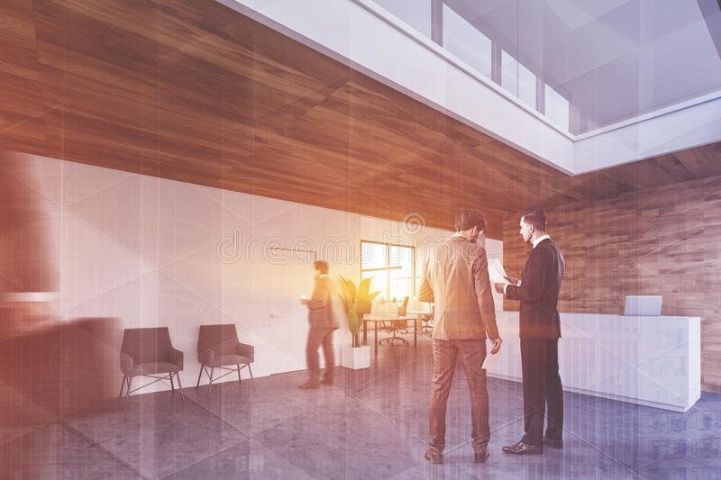 People in office waiting room with reception. Business people discussing documents in modern office waiting room with white and wooden walls, reception desk and royalty free stock images