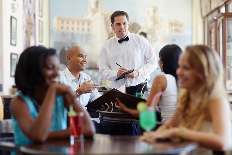 People ordering meal to waiter in restaurant. Young adult hispanic couple dining out in restaurant and talking to waiter in bow tie. Horizontal shape, front view stock photos