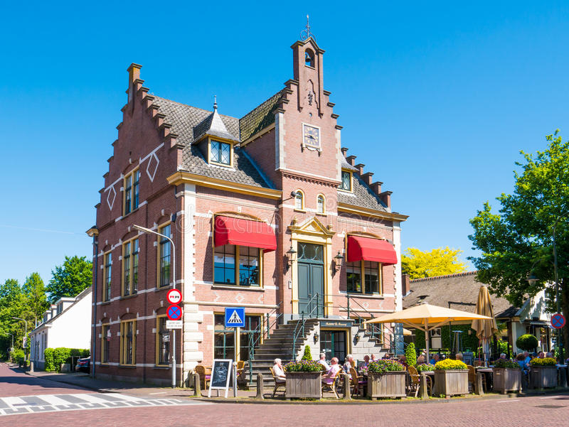 People on outdoor terrace of cafe in old town hall of Laren, Nor. People relaxing on outdoor terrace of restaurant in former town hall of Laren, North Holland royalty free stock photos