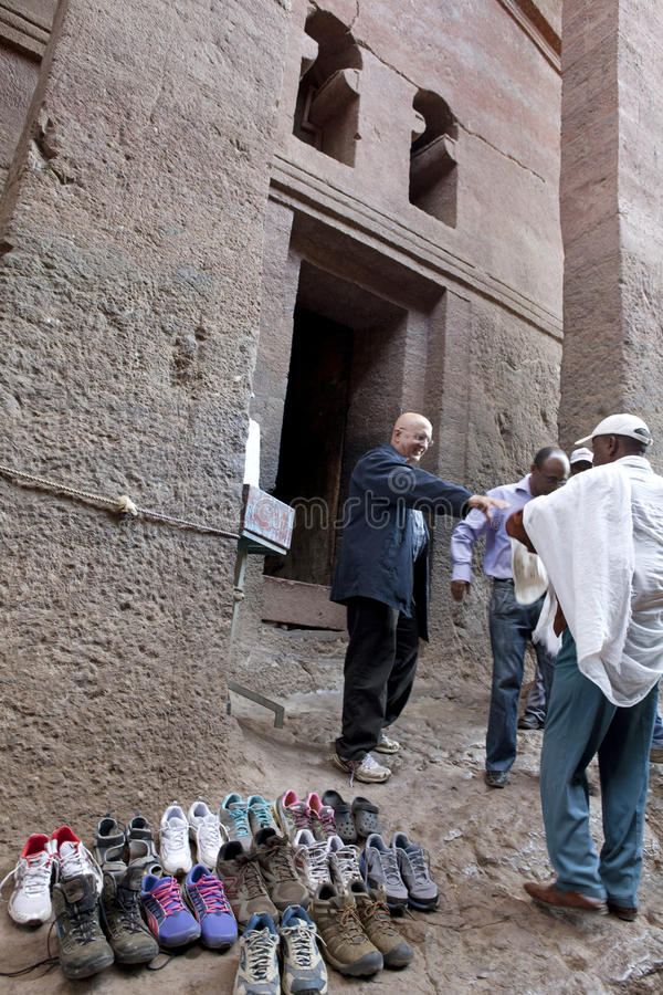 People outside a church, Lalibela. People stood outside a monolithic church in Lalibela. People have also removed their shoes and left them outside the church royalty free stock image