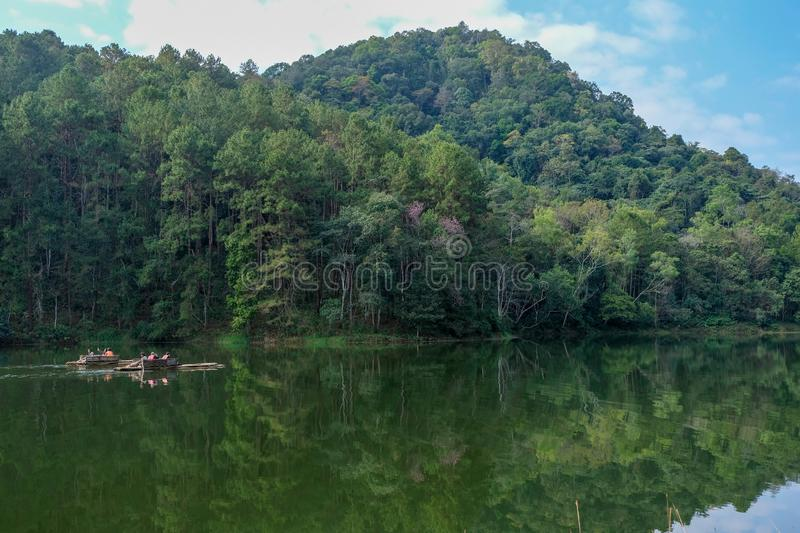 people paddle .Wooden raft in pang ung lake national park with forest background in cloud sky Mae Hong Son royalty free stock photography