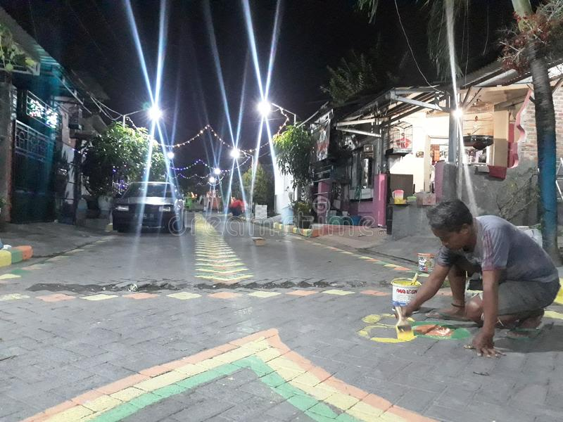 Gresik, East Java / Indonesia - July 28, 2019 : People painted the road to welcome Indonesia`s independence day royalty free stock image