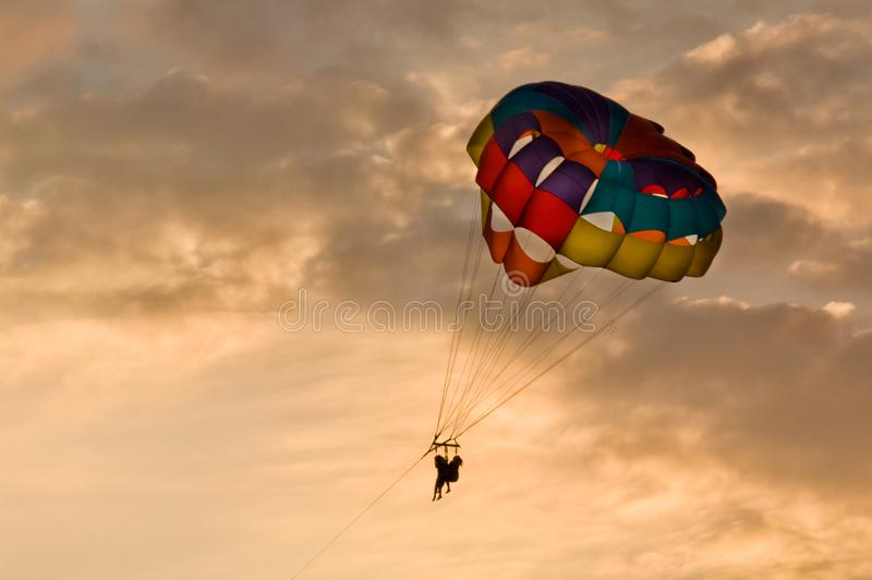 People parasailing at sunset in beautiful light. People parasailing at sunset in beautiful light with a colorful parasail royalty free stock photography