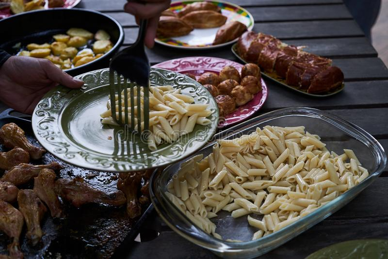 People at a party taking different food, outdoor. Catering buffet food table with baked potatoes, fried chicken legs, pasta and vegetable salad stock images