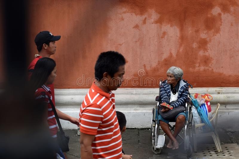 People pass by Ethnic old woman sitting on wheelchair holding Christmas gift box begging for alms at old church yard. San Pablo City, Laguna, Philippines royalty free stock photography