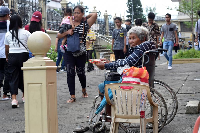 People pass by Ethnic old woman sitting on wheelchair holding Christmas gift box begging for alms at old church yard. San Pablo City, Laguna, Philippines royalty free stock images