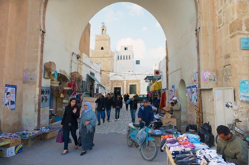 People pass through the medina in Sfax, Tunisia. SFAX, TUNISIA - NOVEMBER 30, 2011: Unidentified people pass through the medina in Sfax, Tunisia stock photo