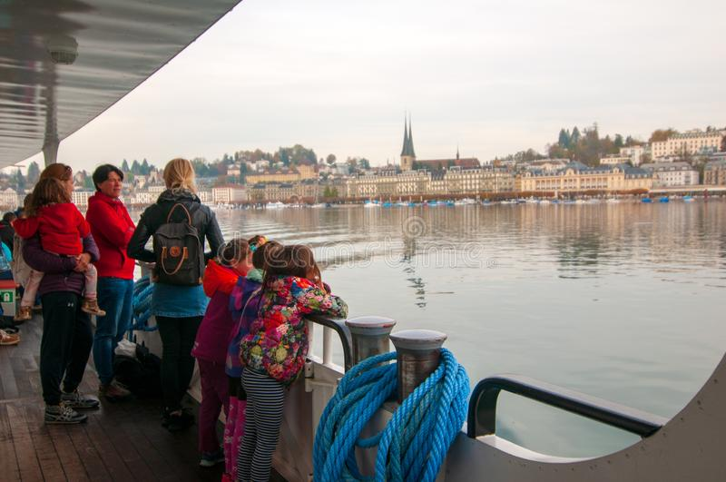 People on a passenger boat on Lake Lucerne with Lucerne city in the back royalty free stock photos