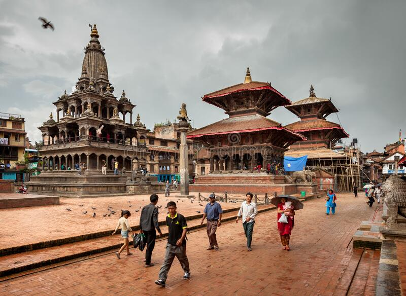 People passing the Patan Durbar Square in Kathmandu of Nepal on a Rainy Day royalty free stock images