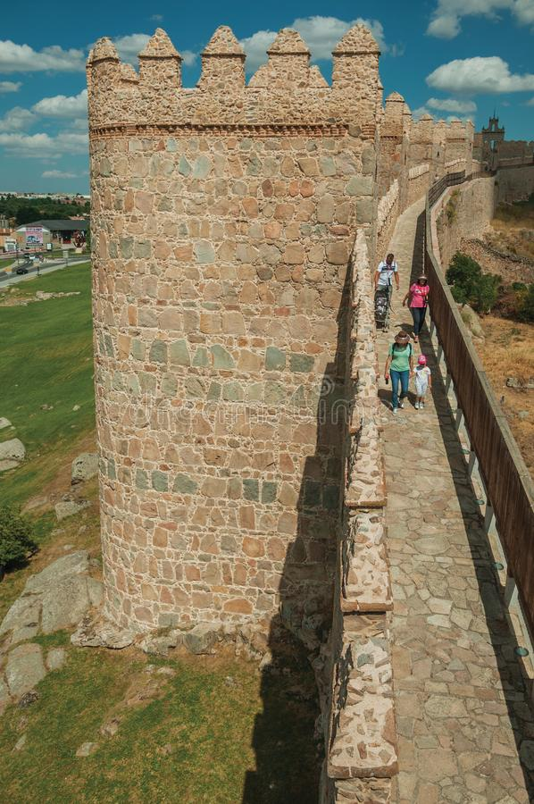People on pathway over stone old thick wall encircling Avila. Avila, Spain - July 22, 2018. People on pathway over stone thick wall with large towers encircling royalty free stock photography