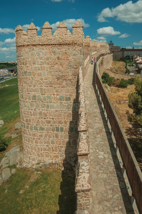 People on pathway over stone old thick wall encircling Avila. Avila, Spain - July 22, 2018. People on pathway over stone thick wall with large towers encircling royalty free stock image