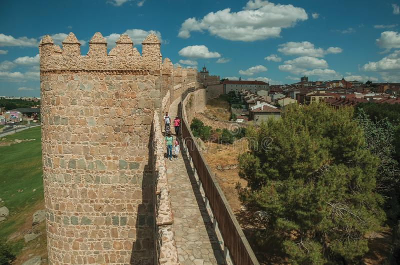 People on pathway over stone thick wall encircling Avila. Avila, Spain - July 22, 2018. People on pathway over stone thick wall with large towers encircling stock images