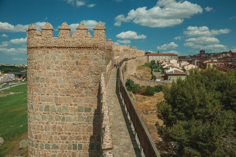 People on pathway over stone thick wall encircling Avila. Avila, Spain - July 22, 2018. People on pathway over stone thick wall with large towers encircling royalty free stock photo
