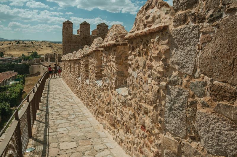 People on pathway over stone thick wall encircling Avila. Avila, Spain - July 22, 2018. People on pathway over stone thick wall with large towers encircling stock image