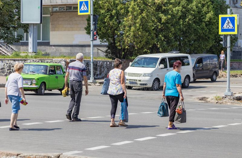 People at the pedestrian crossing. Cross the road in accordance with the rules of the road to ensure the safety of movement in the designated place and the stock photos