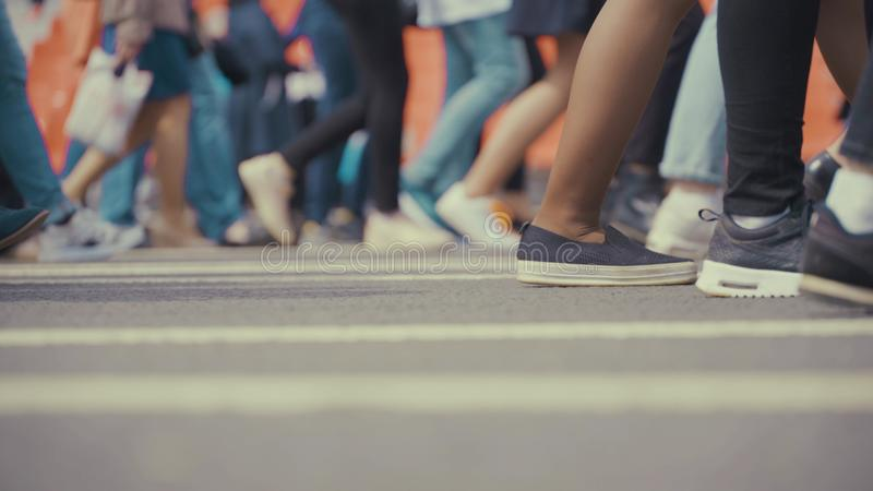 People pedestrians walks across a busy city street.  stock images