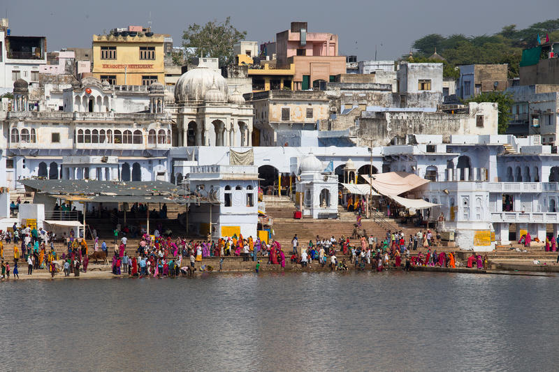 People perform puja - ritual ceremony at holy Sarovar lake. Pushkar - famous worship place in India. PUSHKAR, INDIA - OCTOBER 26, 2014: Unidentified people royalty free stock photography