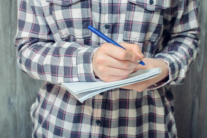 People person essay college high school student education learning concept. Close-up photo of student`s hand writing in notebook. On grey wooden background royalty free stock image
