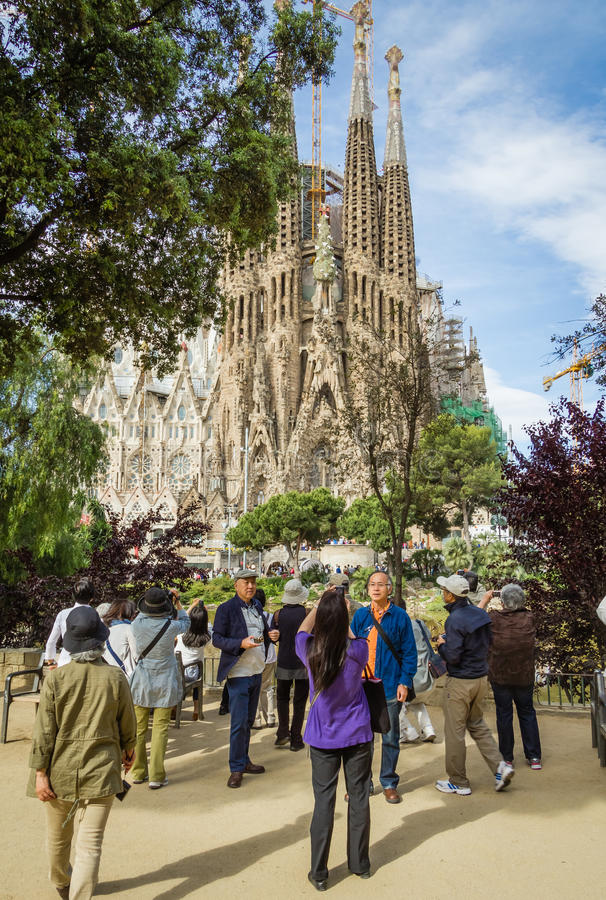 People photograph Sagrada Familia cathedral, designed by Antoni stock photo