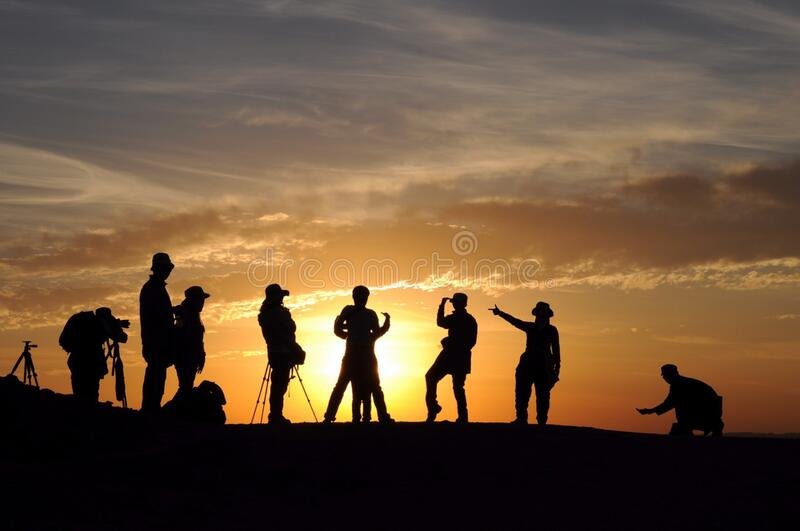 People photographing sunset stock images