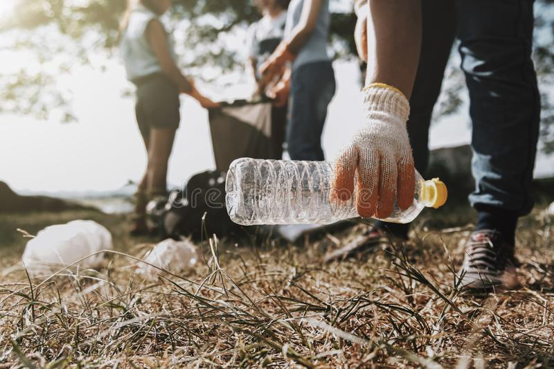People picking up garbage and putting it in plastic black bag for cleaning. Trash, volunteer, litter, volunteering, waste, green, food, rubbish, bin stock photography