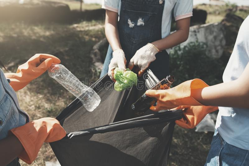 people picking up garbage and putting it in plastic black bag for cleaning at park stock image