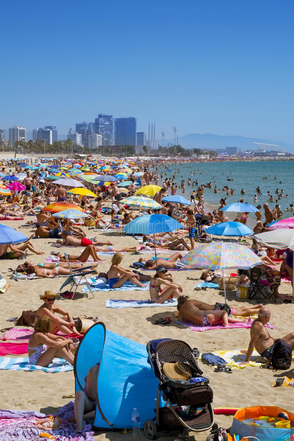 People at Platja del Bogatell beach, in Barcelona, Spain. BARCELONA, SPAIN - JULY 10: Sunbathers at Platja del Bogatell beach on July 10, 2016 in Barcelona royalty free stock images