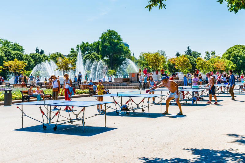 People play ping pong in Moscow Gorky park. Moscow, Russia. 12th July 2014: People play ping pong by the main fountain of Moscow Gorky park. The summer is hot stock image