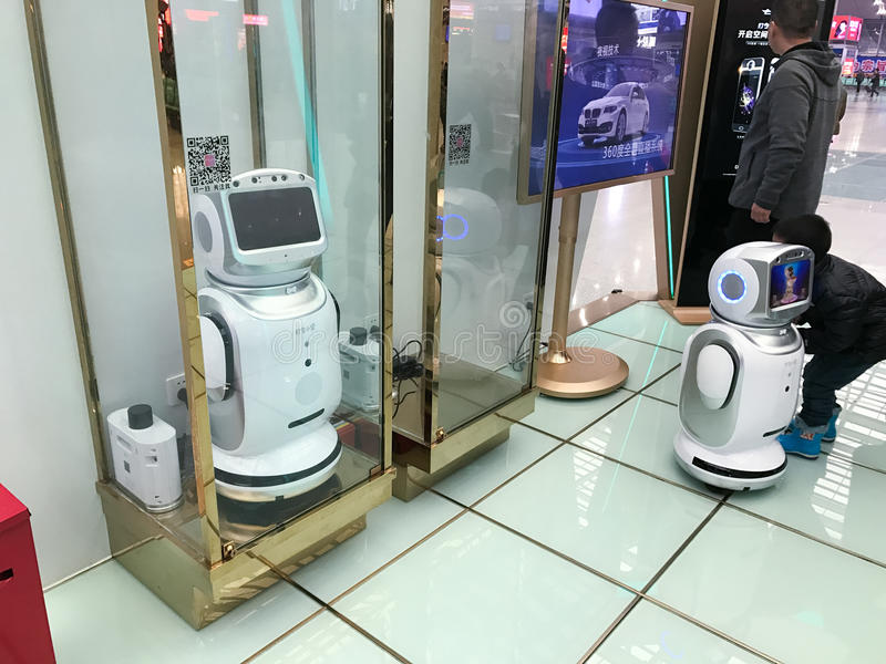 People play with promotion robots in hall stock photos