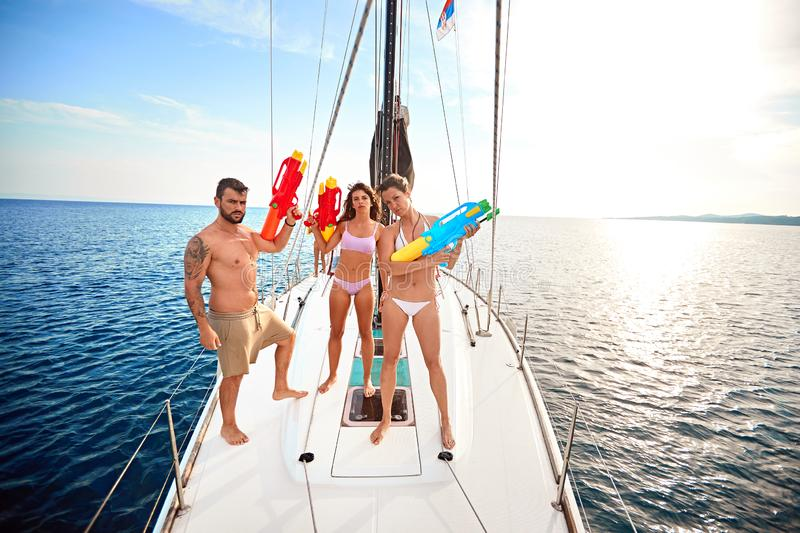 People play on sailing boat with water pistols at vacation stock image