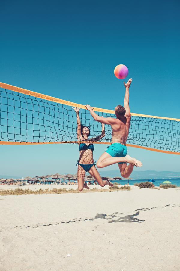 People playing beach volleyball having fun in sporty active lifestyle. Man hitting volley ball in game in summer. Woman royalty free stock photos