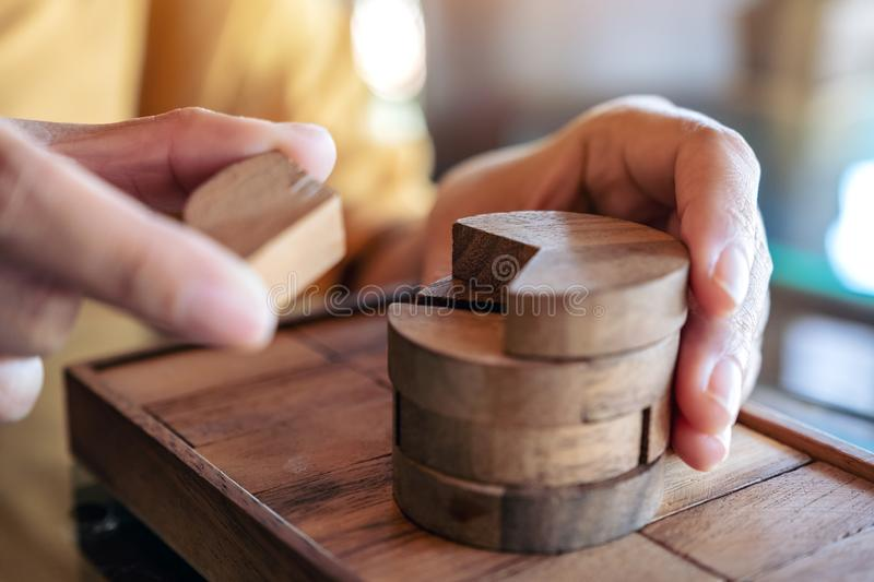 People playing and building round wooden puzzle game. Closeup image of people playing and building round wooden puzzle game stock image