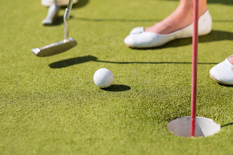 People playing miniature golf outdoors royalty free stock photo