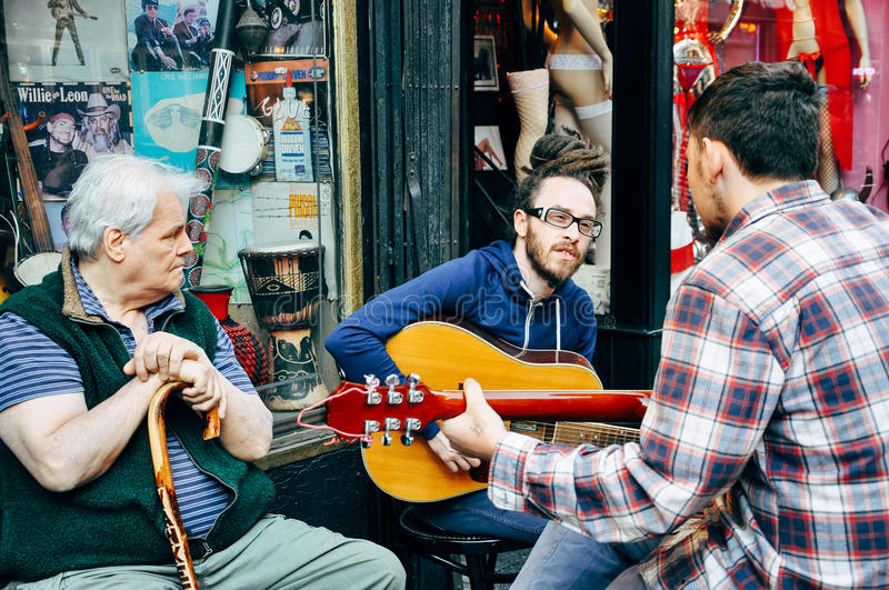 People playing music in front of a vintage music store in Greenwich Village. stock photos