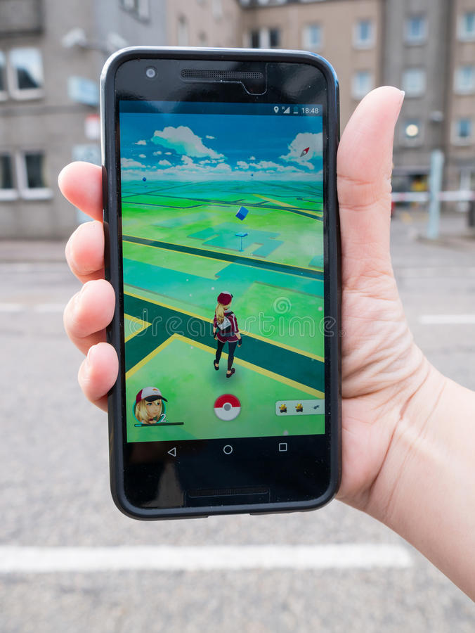 People playing Pokemon GO the hit augmented reality smart phone app stock photo