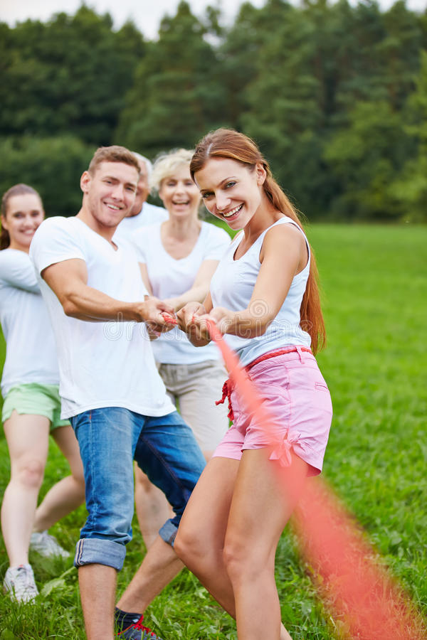 People playing tug of war with rope stock photos