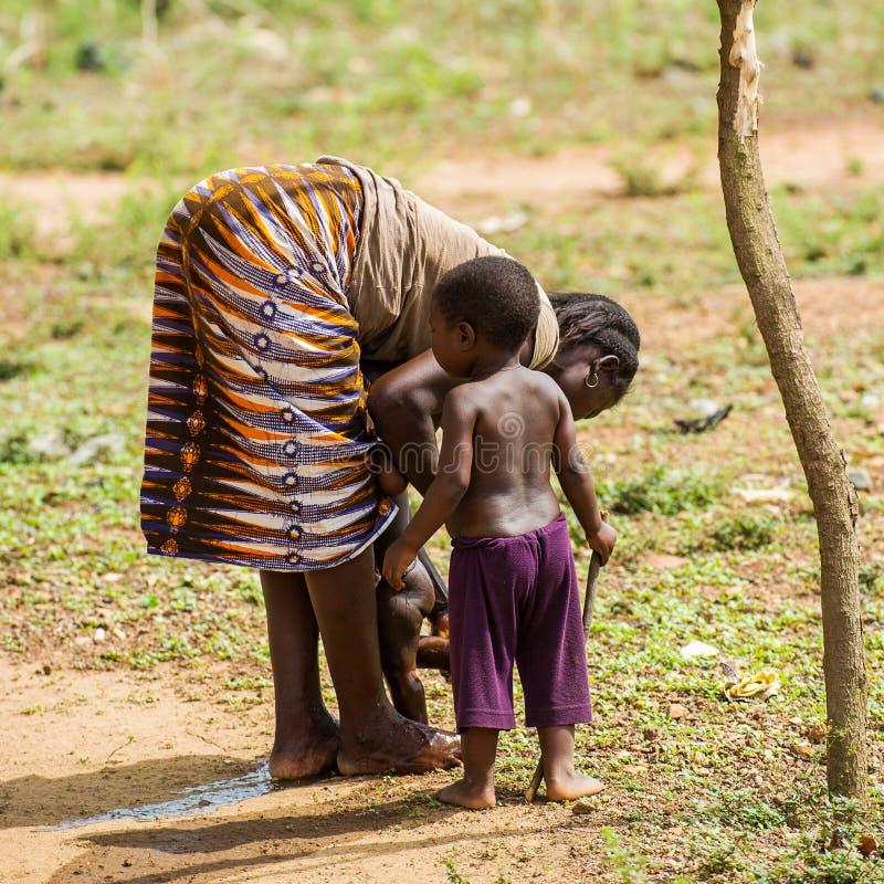 People in PORTO-NOVO, BENIN. PORTO-NOVO, BENIN - MAR 8, 2012: Unidentified Beninese woman plays with her children. People of Benin suffer of poverty due to the stock photos