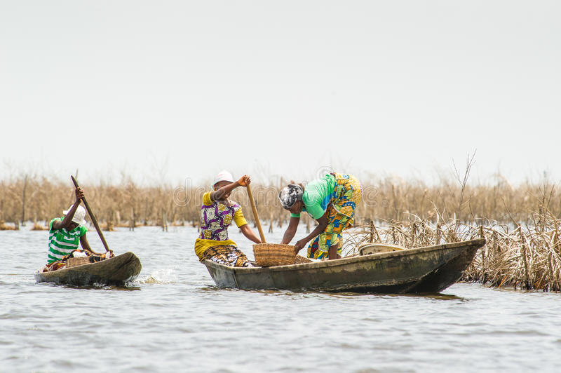People in PORTO-NOVO, BENIN. PORTO-NOVO, BENIN - MAR 9, 2012: Unidentified Beninese woman sail in a fishing boat. People of Benin suffer of poverty due to the stock photography