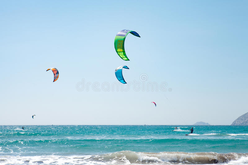 People practicing Kitesurfing. Beach on the peninsula Prasonisi, Rhodes. Colorful kites on the sea shore. Blue sea and royalty free stock photos