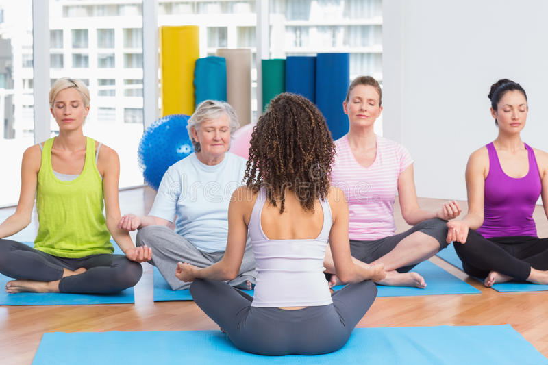 People practicing lotus position in yoga class. Group of people practicing lotus position in yoga class stock photography