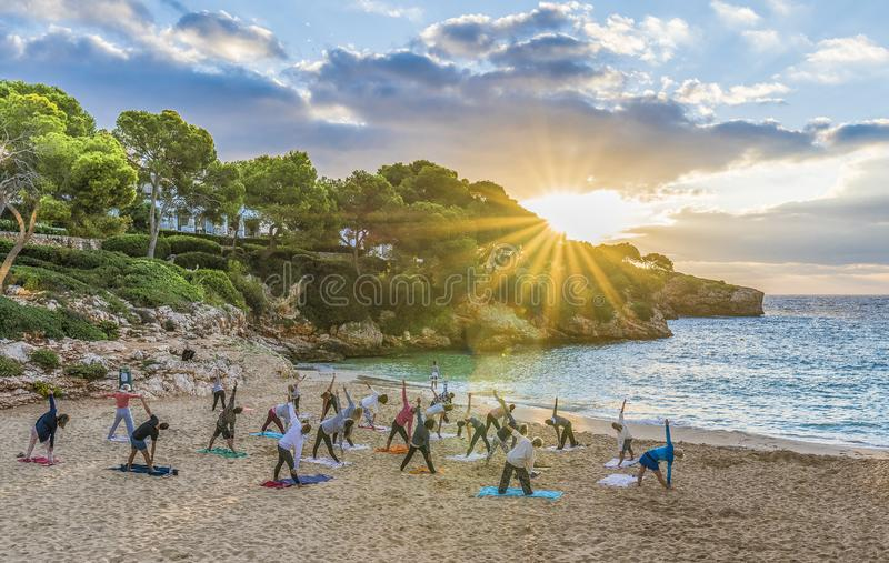 People practicing yoga at sunset time, Palma Mallorca Island, Spain stock image