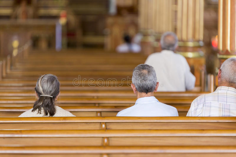 People praying at the church of Guatape in Cololmbia. Rear view of Colombian people sitting and praying at the church of Guatape, Colombia 2015 royalty free stock photography