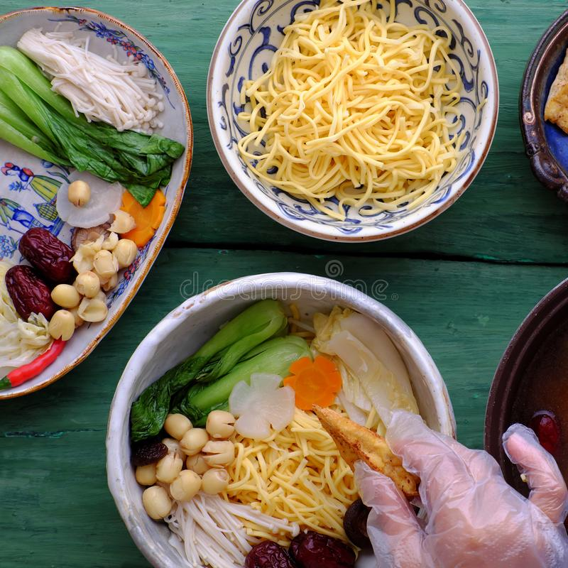 People prepare vegetarian homemade noodle soup bowl from vegan ingredient. People prepare Vietnamese vegetarian homemade noodle soup bowl from vegan ingredient stock photo